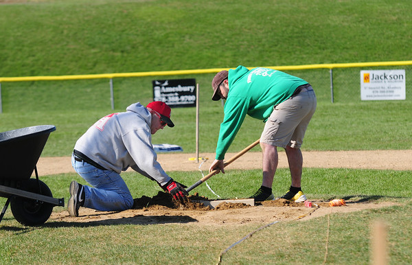 JIM VAIKNORAS/Staff photo  Chard Ayers and Dave MacDonald work of one of the pitcher's mounds at the Little League field at the Cashman School in Amesbury Saturday.