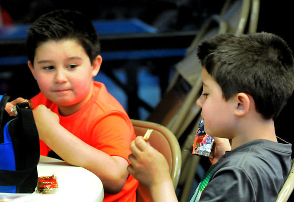 BRYAN EATON/Staff Photo. Twins Aydan Ameida, 8, left, and Adryan take a snack break from games in the gymnasium at the Seabrook Rec Center. The center is open days this week as New Hampshire schools are on break.