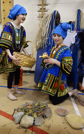 BRYAN EATON/Staff Photo. Ellie Gay-Killeen, left, and Mia Berardino, both 12, portray members of the Dogon Tribe of Africa and are preparing a fire for dinner. Sixth-graders at the Pine Grove School held an African Festival highlighting the culture they've learned to visiting parents.