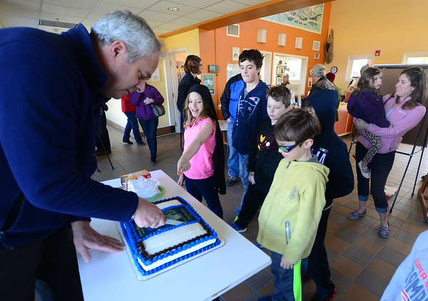 JIM VAIKNORAS/Staff photo  Director of its Joppa Flats Education Center  David Moon, cut a cake at the 100th Day Celebration at teh center Saturday.