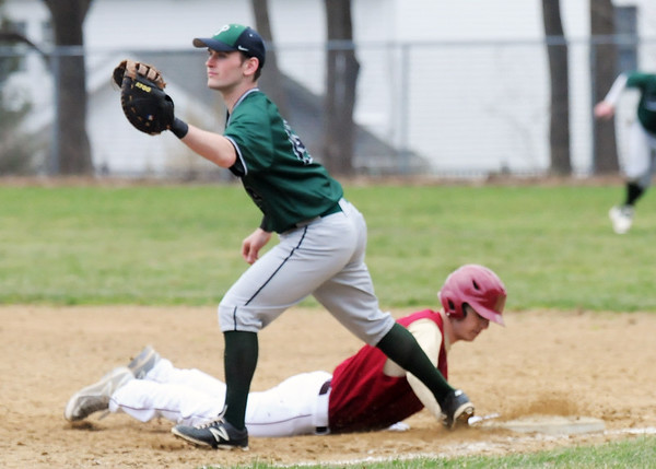 BRYAN EATON/Staff Photo. Pentucket first baseman Liam O'Neil waits for the throw as Newburyport's Wolbach makes it back to base.