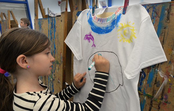 "BRYAN EATON/Staff Photo. Riley Freeman, 8, marks the world's continents on her t-shirt with other drawings such as the dolphin at left in Pam Jamison's art class at the Bresnahan School in Newburyport. The second-graders are having an event ""Spotlight on Second Grade"" where they will perform songs and wear the t-shirts they decorate, each class with a different theme on what they've been studying."