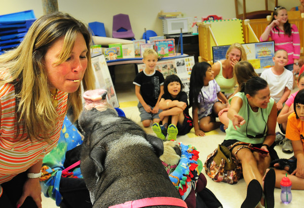 """Newburyport: Nicole Brennan, director of the YWCA Children's Center gives an apple chip in her lips for a kiss with Daisy the Potbellied Pig. Farmer Minor and Daisy visited the center for a program """"Pig Out on Reading"""" to get children more interested in books. Bryan Eaton/Staff Photo"""