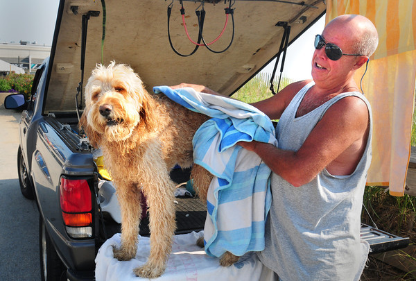 Salisbury: Wayne Knipe of Seabrook wipes off Shamus after a swim in the ocean at Salisbury Beach. He wasn't so much wiping him dry, as rubbing the sand out of his fur to keep it from the seat of his truck. Bryan Eaton/Staff Photo