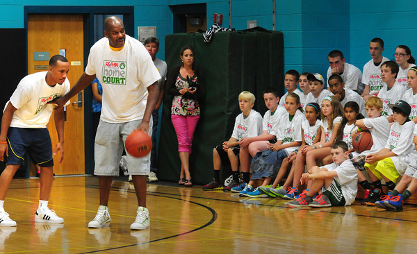 Merrimac: Boston Celtics forward Avery Bradley, left, and former player Cedric Maxwell show youngsters at a basketball clinic at the Donaghue School in Merrimac some defensive moves. Bryan Eaton/Staff Photo