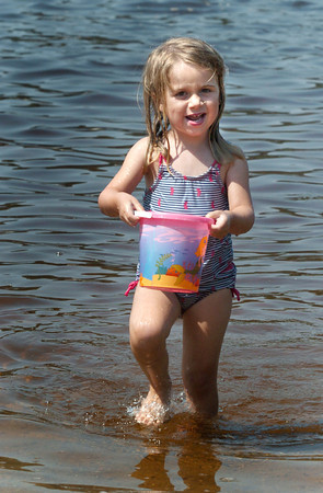 """Amesbury: Anna Nazzaro, 4, of Amesbury brings water back to her brother, Matthew, 5, who was digging a hole in the ground at Lake Gardner Beach yesterday. The two were making, in the words of Anna, """"yucky ducky soup."""" Bryan Eaton/Staff Photo"""