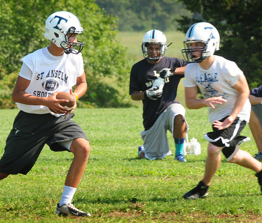 Byfield: Triton quarterback Brad Whitman, left, hands off during practice. Bryan Eaton/Staff Photo