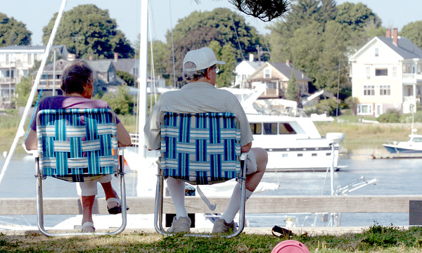 Newburyport: Ruth and Blake Hughes of Newburyport sit in the shade and catch the breeze while watching the boat traffic at Newburyport Waterfront Park on Wednesday afternoon. Bryan Eaton/Staff Photo