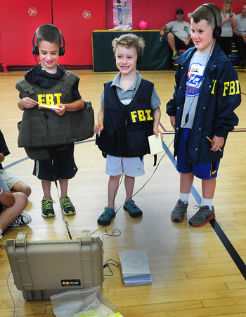 """Newburyport: Newburyport Police ran a camp for youngsters at the Bresnahan School with games, police dog demonstrations and other activities including negotiating a hostage situation led by a representative from the FBI. Here, from left, Eli Raymond, Eddy Bleiken and Cole Eiserman are wired up to """"negotiate"""" with the suspect holding a hostage because he didn't want to do his homework. Bryan Eaton/Staff Photo"""