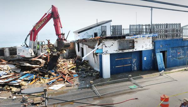 Salisbury: An excavator works its way south demolishing the Sidewalk Cafe at Salisbury Beach. Bryan Eaton/Staff Photo