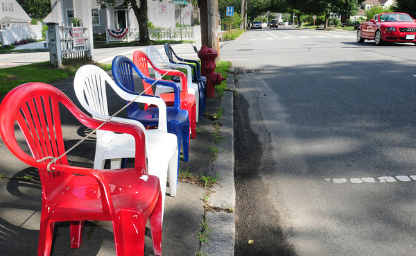 Newburyport: Chairs reserving spots to view the Yankee Homecoming Parade tomorrow are popping up all over High Street in Newburyport, these at the corner of Woodland Street in red, white and blue. Bryan Eaton/Staff Photo