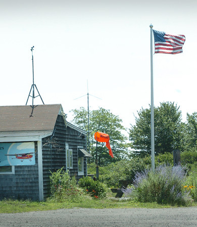 Newbury: A wind sock and American flag show the northeasterly direction of the wind Wednesday at Plum Island Airfield, which kept the temperatures on the cooler side. Bryan Eaton/Staff Photo