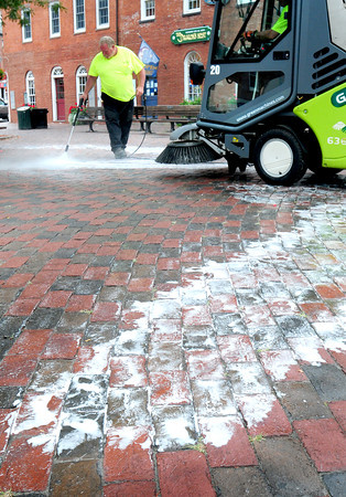 """Newburyport: Alan Frost of the Newburyport Department of Public Services sprays cleaner in Market Square before being scrubbed and vacuumed. Lack of rain has made areas there and on Inn Street gunky with spilled ice cream, etc. and """"snail trails"""" caused when trash bags that can drip, are moved from cannisters to a dump truck. Bryan Eaton/Staff Photo"""