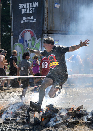 Amesbury:Michael Ives jumps over fire in the Spartan Race at Amesbury Sports Park Saturday. Jim Vaiknoras/staff photo