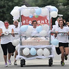 Newburyport: Elements Massage, their bed covered in balloons, races to the finish the Yankee Homecoming Lions Club Bed Race on Federal Street. Jim Vaiknoras/staff photo