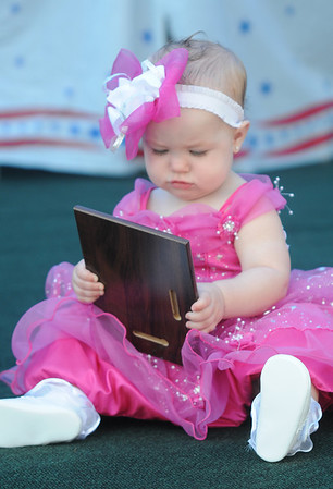 Seabrook: Winner of Most Photogenic baby, Ashlin Turcotte, checks out her plague at Old Home Day at the Walton School in Seabrook Saturday. Jim Vaiknoras/staff photo