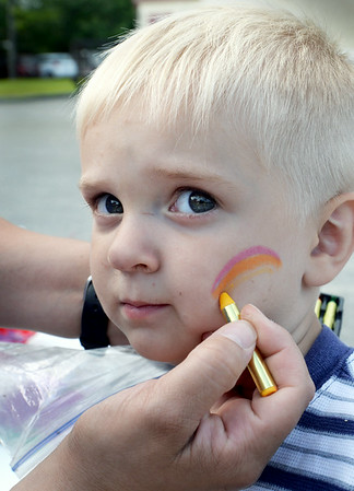 BRYAN EATON/Staff Photo. Mike Watkins, 2, gets his cheek adorned by a face painter, Andrea Watkins, who happens to be his mother. They were at an event at the Hilton Center in Salisbury hosted by the East Parish United Methodist Church which had different events for children including a hot dog dinner and a concert by the Merrimack Valley Concert Band on Tuesday night.