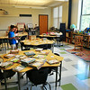 BRYAN EATON/ Staff Photo. Alexandra Sullivan, left, and Delaney Woekel, both 8, help organize books in Mary Ellen Hoiseth's first grade class at the new Bresnahan School. The two were in her second grade class last year.