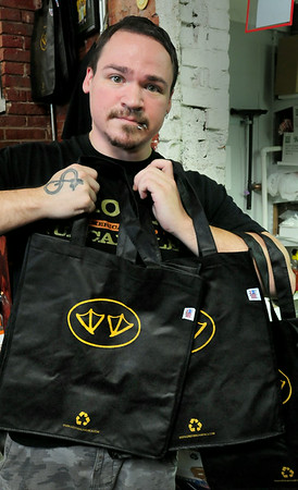 BRYAN EATON/ Staff Photo. Brandon Wiley shows off reusable shopping bags that the Black Duck Market and Deli in the Tannery sell for 99 cents, as do many larger supermarkets.