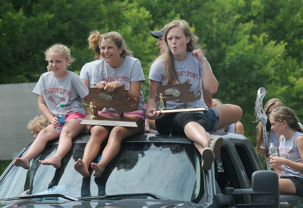 JIM VAIKNORAS/Staff photo Members of the 2014 State Championship lacross team ride in  in the Yankee Homecoming Parade on High Street in Newburyport Sunday. behind them was a truck carrying the State Chapmionship Girls Soccer Team.
