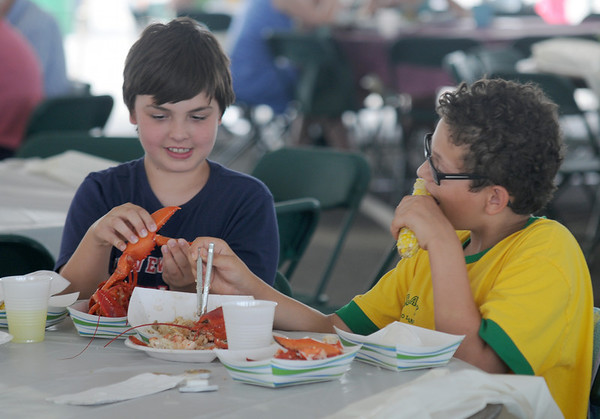 JIM VAIKNORAS/Staff photoCharlie Ives and Eamonn Sullivan enjoy lobsters and corn at the Newburyport 250th Clam Bake at Plum Island point Sunday afternoon.
