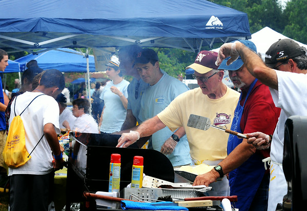 JIM VAIKNORAS/Staff photo Volunteers flip burger for Opportunity Works  at Family Day at Maudslay in Newburyport Saturday.
