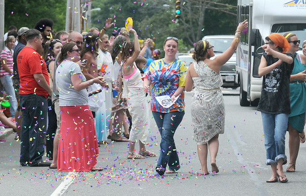 JIM VAIKNORAS/Staff photo Revelers in tie dye shirts and togos dance with confetti at the Yankee Homecoming Parade on High Street in Newburyport Sunday.