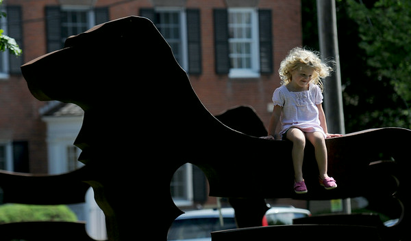 JIM VAIKNORAS/Staff photo Myra Taffel,3, sits on one of Dale Rogers Big Dog Sculptures at the Bartlet Mall in Newburyport. The Dogs will remain at the Mall through August 24th.