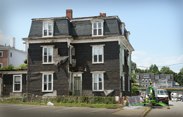 BRYAN EATON/Staff Photo. The siding covering the original clapboards to this building at 83 Merrimac Street in Newburyport was taken down as the building is prepared to be demolished.