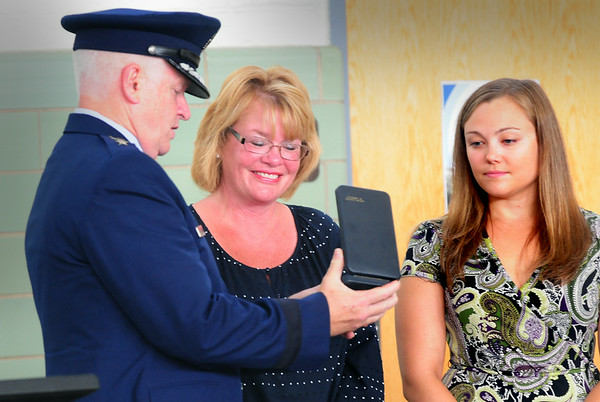 BRYAN EATON/ Staff Photo. Holly Shay smiles as Major General L. Scott Rice presents the Massachusetts Medal of Liberty for her son US Army Sgt. Jordan Shay who died in Iraq in 2009. Shay's fiancee Kelsey Chandonnet is at right.