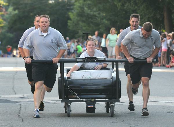 JIM VAIKNORAS/staff photo THe Newburyport Police Dept head to the finish line at the Lions Club Bed Race on Federal Street in Newburyport.