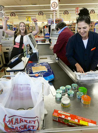 BRYAN EATON/ Staff Photo. Newburyport Market Basket's Joann GIlbert, and Jacqueline Sollazzo, right, check out Rachel Hickey as she shows her joy at the resolution of the Market Basket saga. Hickey, from Salisbury, had been boycotting the grocery chain.
