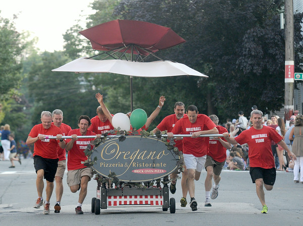 JIM VAIKNORAS/staff photo The Meatball Team from Oregano Pizzeria roll to the finish line at the Lions Club Bed Race on Federal Street in Newburyport.