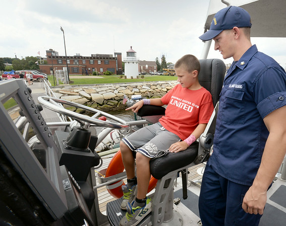 BRYAN EATON/ Staff Photo. US Coast Guard Petty Officer Devin Brown shows the controls of the motor lifeboat to Joshua Paige, 9, of Merrimac during Station Merrimack's open house yesterday.