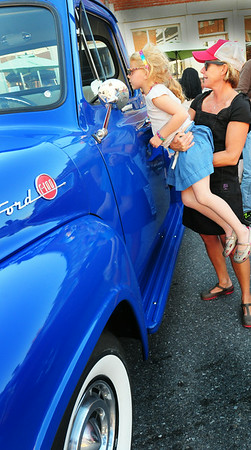 BRYAN EATON/Staff Photo. Phoebe Whitcomb, 6, of Newburyport gets a lift from mom, Lynn, to peek into a 1955 Ford 100 pickup truck at the Newburyport Car Show last night in the downtown.