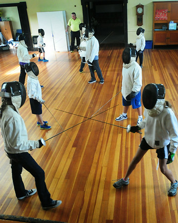 BRYAN EATON/ Staff Photo. Children practice their moves in fencing at the Belleville Church hall on Thursday morning.  Jack Mullarkey of the 3MB Fencing Club, who teaches on a regular basis there on Saturdays, was conducting the week-long camp for the Newburyport Youth Services.