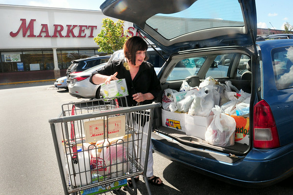 BRYAN EATON/ Staff Photo. Joellen Morse of Newburyport loads up her hatchback at the Market Basket in Newburyport as the long desolate parking lot started filling up with cars again.