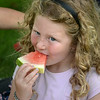 BRYAN EATON/ Staff Photo. Neve Cummings, 6, of Newburyport gets a piece of watermelon for dessert after lunch at Kids Day in the Park.