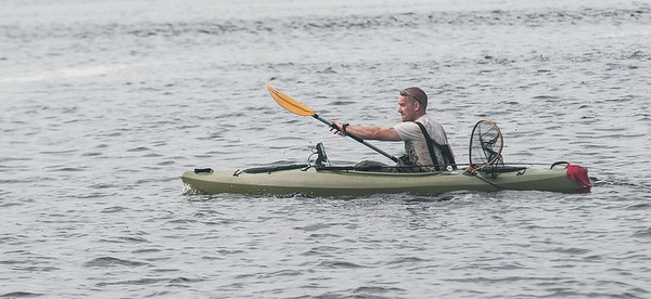 JIM VAIKNORAS/Staff photo A fisherman in a kayak paddles across the Maerrimack off Plum Island point .