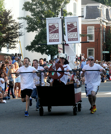 JIM VAIKNORAS/staff photo Mayor Holaday stears the Newburyport 250th bed at the Lions Club Bed Race on Federal Street in Newburyport.