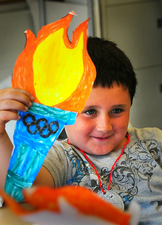 BRYAN EATON/Staff Photo. Jack Staunton, 7, of Newburyport shows off his Olympic torch he made in the art room at the Boys and Girls Club. The youngsters did different Olympic events and made their own medals as well as the paper torches.