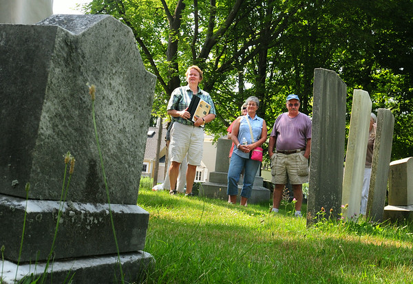 BRYAN EATON/ Staff Photo. Ghlee Woodworth, left, leads the Cemetery Crawl at Highland Cemetery. She show gravestones here of members of the Pearson family which owned a bakery that made hardtack for the sailing industry in the 1800's.