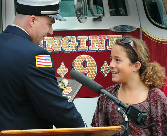 BRYAN EATON/ Staff Photo. Newbury Fire Lt. Jonathan Kelley shakes Collette Crooks' hand as he presents her with a citation. The ten year-old from Rowley rescued a four year-old boy from the water at Sandy Point on Plum Island last week.