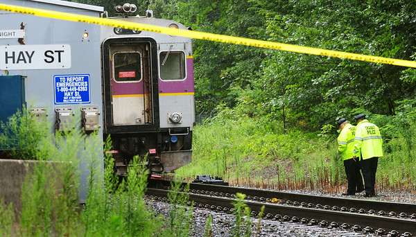 BRYAN EATON/Staff Photo. Transit police check out the railbed yards from the Hay Street crossing in Newbury after a woman's body was seen by staff on the train in photo that was heading to the Newburyport station.