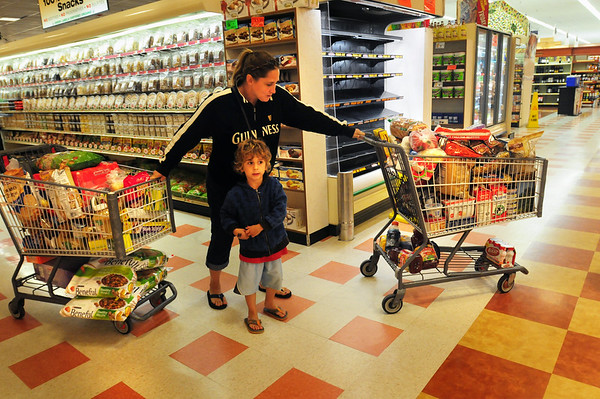 """BRYAN EATON/ Staff Photo. Candace Platt of Amesbury, with son Peter, 4, has two carts filled with food and supplies at the Market Basket at Southgate Plaza in Seabrook. She calls herself a """"stockpiler"""" and had been boycotting along with many other customers."""