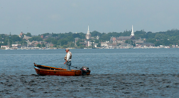 JIM VAIKNORAS/Staff photo A fisherman makes his way across the Merrimack River with the Newburyport skyline in teh back ground earlier this week.