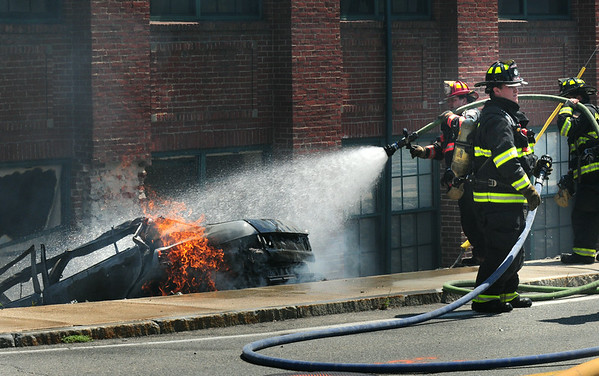 BRYAN EATON/ Staff Photo. Amesbury firefighter hose this car that crashed into Hatter's Point Condominiums in Amesbury. The driver and a dog in the vehicle died in the early afternoon crash.