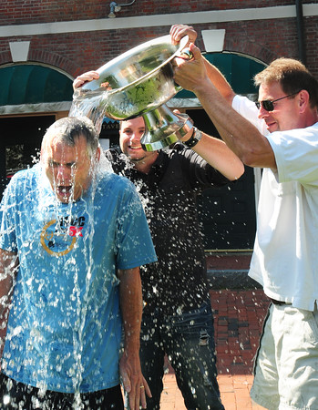 """BRYAN EATON/ Staff Photo. Rev. David Beaty of River Oaks Community Church in Clemmons, N.C. takes the """"ice bucket challenge"""" from a champagne bucked poured by Garrison Inn staff Chris Shipulski, center, and Stu Cunningham on Wednesday morning. Beaty is up on sabbatical and had been staying at the inn for several days with his family. He loves Newburyport and has visited before and took interest in the Old South Church where Rev. George Whitfield, an evangelist of note, is buried."""
