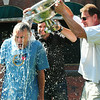 "BRYAN EATON/ Staff Photo. Rev. David Beaty of River Oaks Community Church in Clemmons, N.C. takes the ""ice bucket challenge"" from a champagne bucked poured by Garrison Inn staff Chris Shipulski, center, and Stu Cunningham on Wednesday morning. Beaty is up on sabbatical and had been staying at the inn for several days with his family. He loves Newburyport and has visited before and took interest in the Old South Church where Rev. George Whitfield, an evangelist of note, is buried."