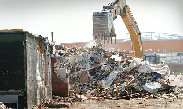 BRYAN EATON/ Staff Photo. The principal's office still stands for now,  at left, as the front end loader rips out the cafeteria of the old Bresnahan School, the new school visible in back.
